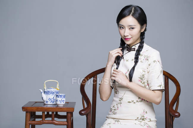 Chinese woman in traditional cheongsam with tea set — Stock Photo