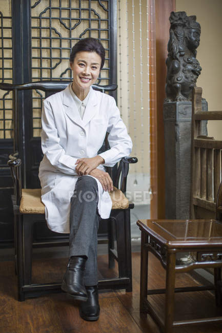 Female Chinese doctor sitting in chair and looking in camera — Stock Photo