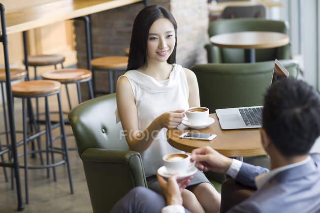 Китайський чоловік і жінка говорити в кафе з чашок кави — стокове фото
