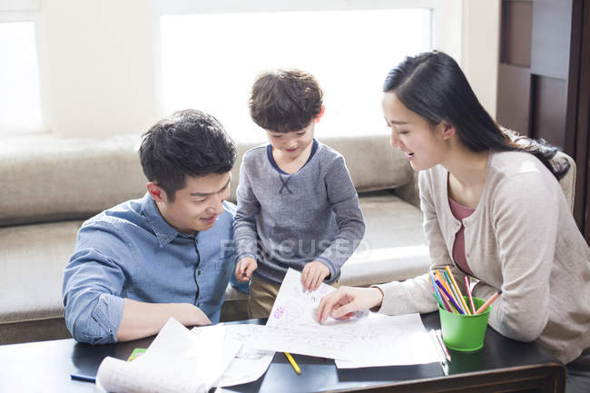 Chinese parents helping son with homework — Stock Photo
