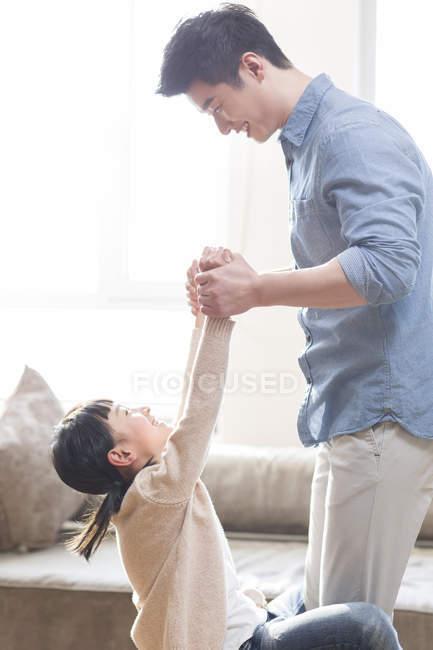 Père et fille chinois tenant la main et jouant à la maison — Photo de stock