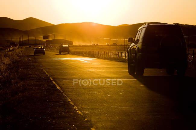 Автомобили на проселочной дороге с живописным видом на закат в плато Басанг, Китай — стоковое фото