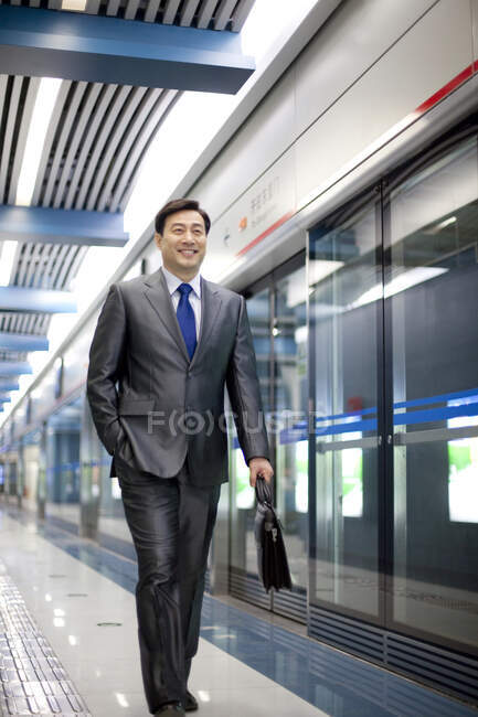 Chinese businessman walking with suitcase in airport scene — Stock Photo