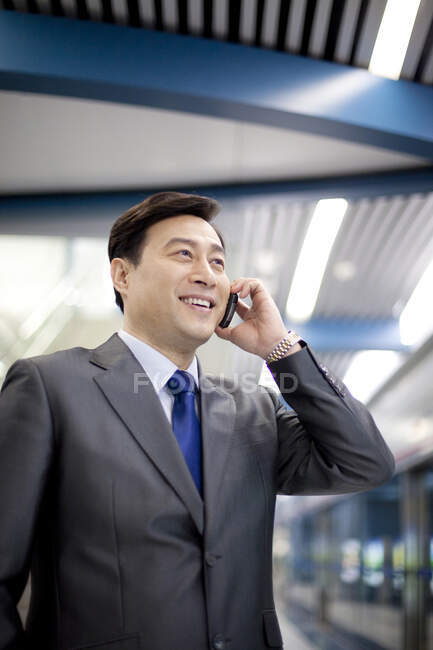 Chinese businessman calling on phone in airport scene — Stock Photo