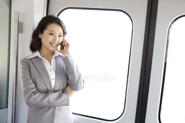 Young chinese businesswoman calling on phone by windows — Stock Photo