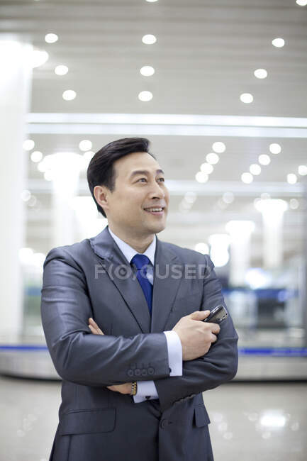 Portrait of Chinese businessman in airport scene — Stock Photo