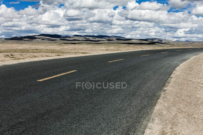 Road with mountains view and cloudy sky, Qinghai Province — Stock Photo