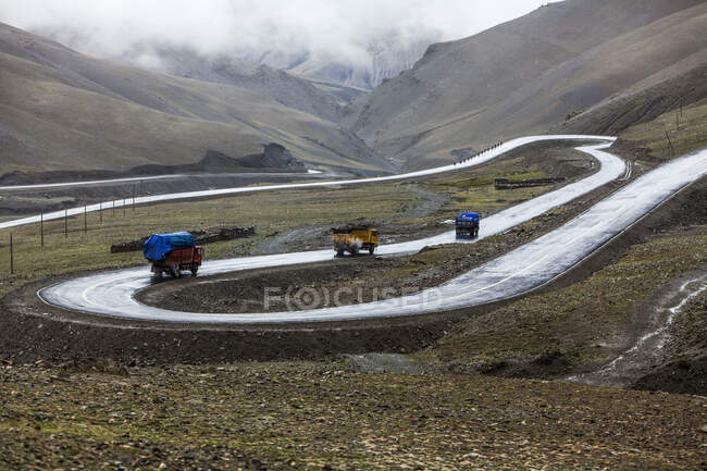 Грузовики на дороге в Тибете горный пейзаж, Китай — стоковое фото