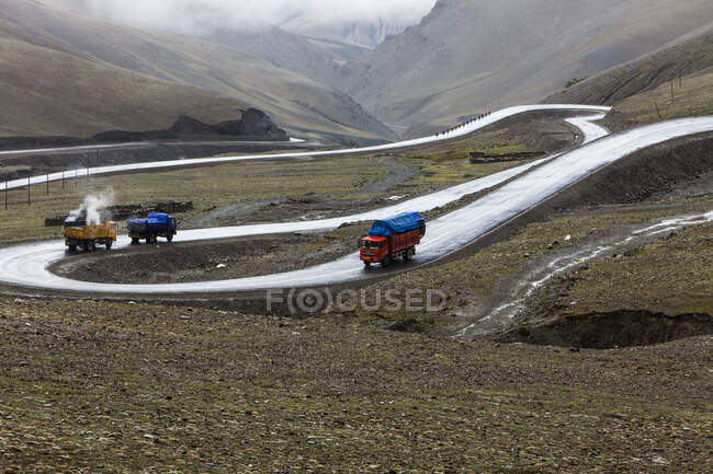 Trucks on road in Tibet mountainous landscape, China — Stock Photo