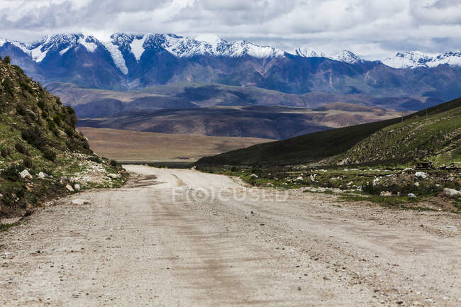 Road with mountains view and cloudy sky, Tibet, China — Stock Photo