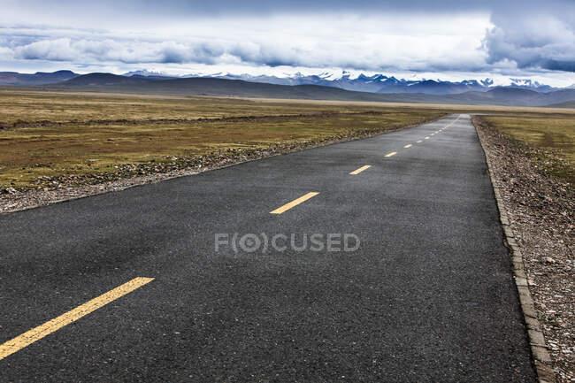 Дорога з гірським видом і хмарним небом, Тибет, Китай — стокове фото