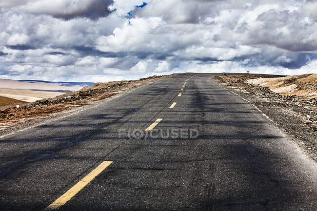 Road with cloudy sky, Tibet, China — Stock Photo