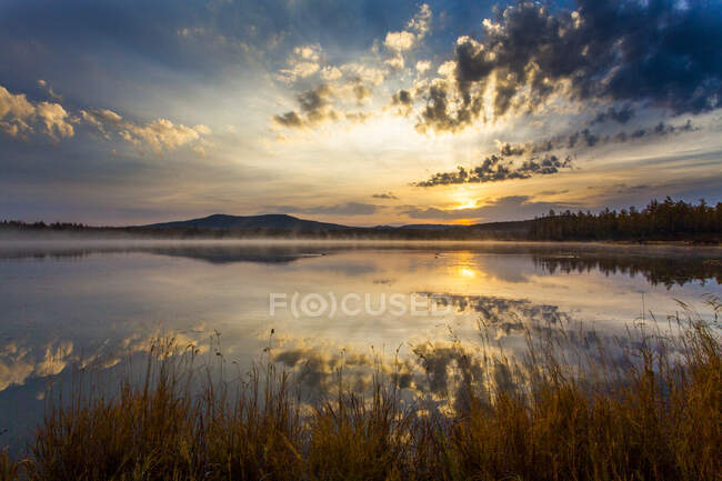 Lake with sunset sky reflection and mountains — Stock Photo