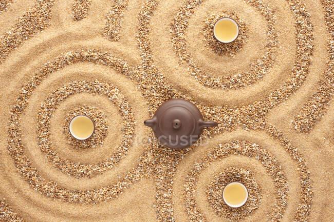 Vue de la théière et des tasses sur la surface du sable — Photo de stock