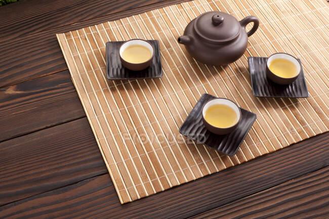 Китайський керамічний чай, наповнений горщиками на бамбукових матах. — стокове фото