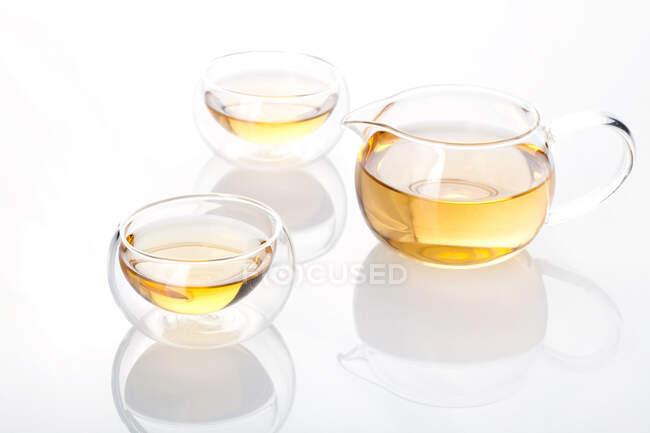 Набор чая из стекла с чайником и чаем в чашки изолированы на белом фоне — стоковое фото