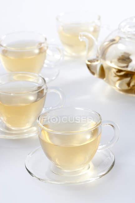 Glas-Tee-Set mit Kanne und Tee in Tassen isoliert auf weißem Hintergrund — Stockfoto