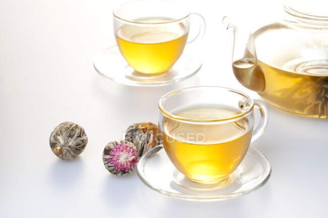 Скляний чай з горщиком і чаєм у чашках, ізольованих на білому тлі. — стокове фото