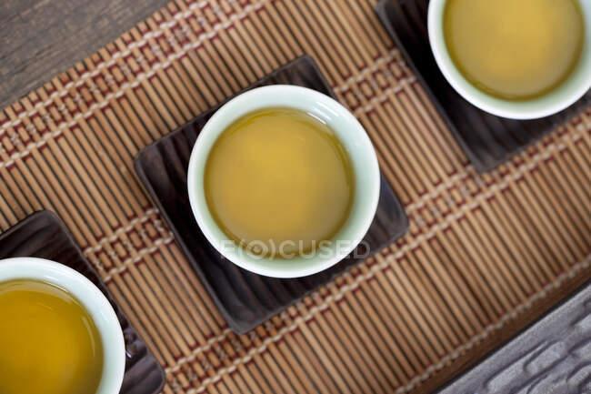 Китайські чашки для чаю на бамбукових матах. — стокове фото