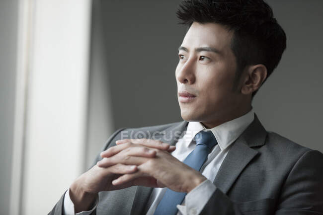 Portrait of young chinese businessman in suit with tie — Stock Photo
