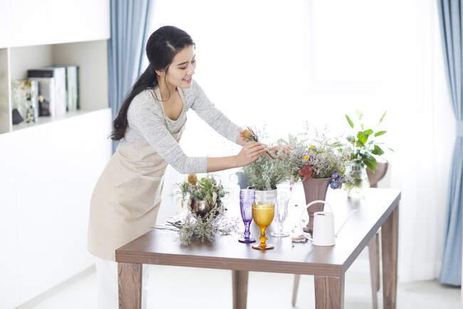 Молодая китаянка собирает цветы дома — стоковое фото