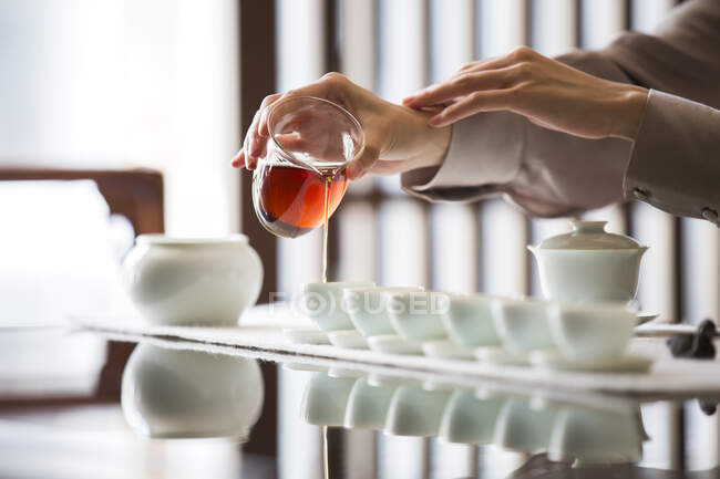 Cropped shot of woman performing tea ceremony, pouring tea — Stock Photo