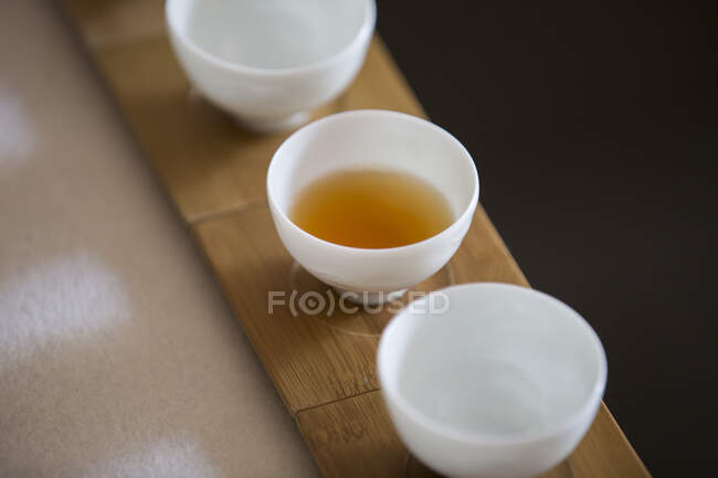 Tea cups, one filled on wooden stands, close up shot — Fotografia de Stock