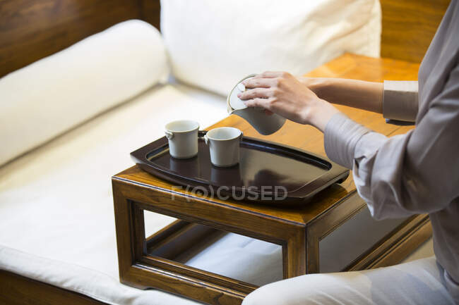 Cropped shot of woman pouring tea in cups from ceramic pot — Stock Photo