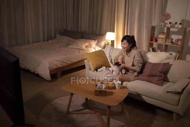 Junge Chinesin spielt Videospiel auf Sofa — Stockfoto