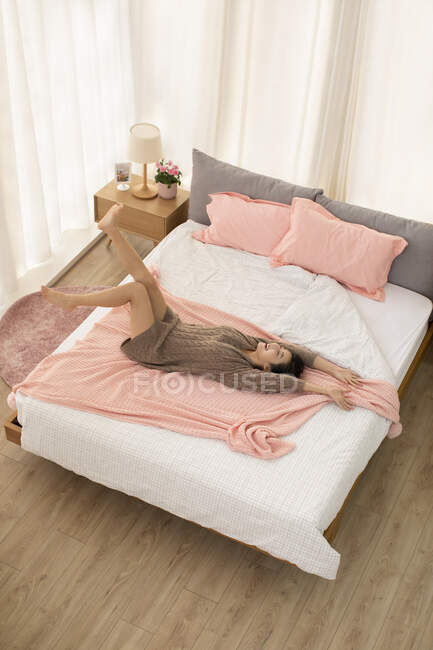 Young chinese woman relaxing on bed — Stock Photo