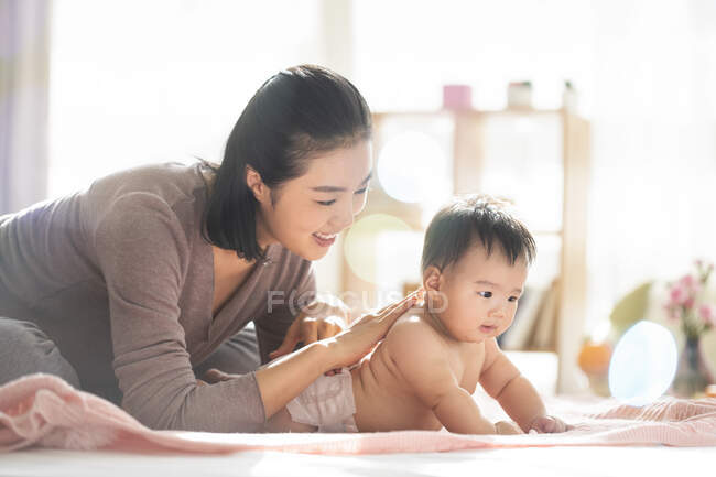 Young chinese mom smiling and playing with baby on couch — стокове фото