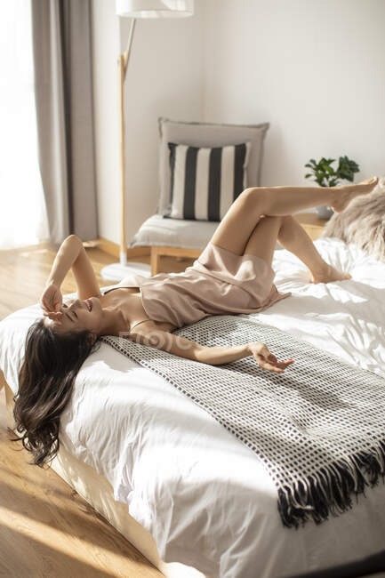 Счастливая китаянка, лежащая на кровати под утренним солнцем и смеющаяся — стоковое фото
