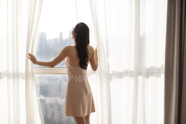 Young Chinese woman opening curtains on window, morning sunlight — Stock Photo