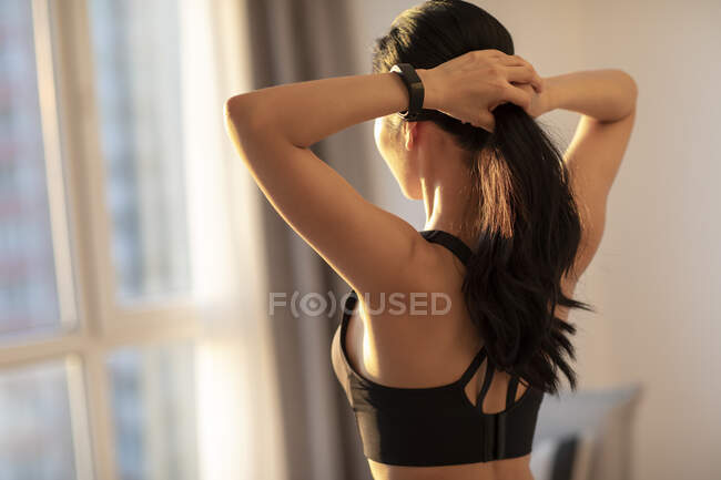Rear view of young woman in sportive clothes tying hair in morning sunlight — Stock Photo