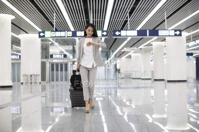 Young woman walking with luggage in airport and looking on hand watch — Stock Photo