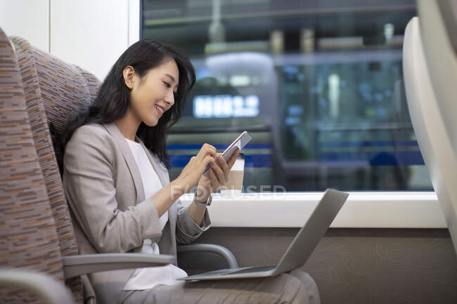Woman sitting in high-speed train with laptop and using smartphone — Stock Photo