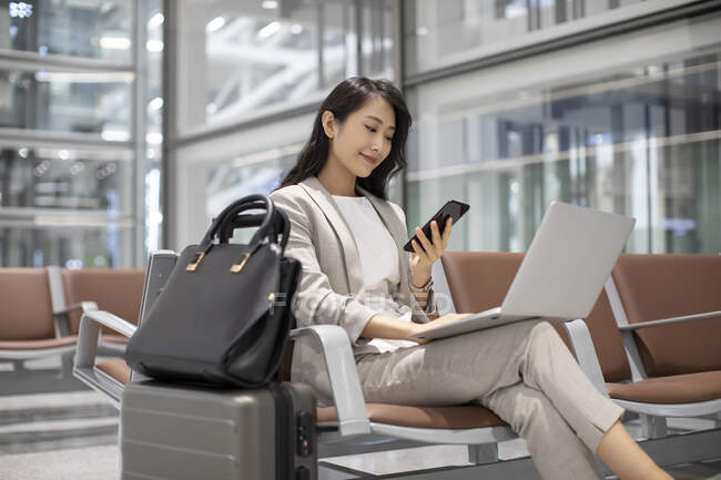 Woman using smartphone while sitting in airport with laptop — Stock Photo