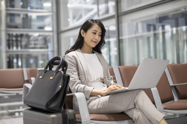 Woman using laptop while sitting in airport — Stock Photo