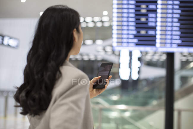 Young chinese woman using smartphone in airport — Stock Photo