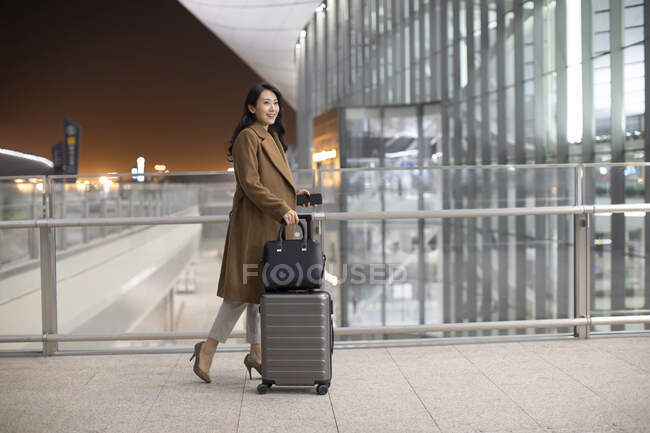 Young woman walking with luggage in airport — Stock Photo