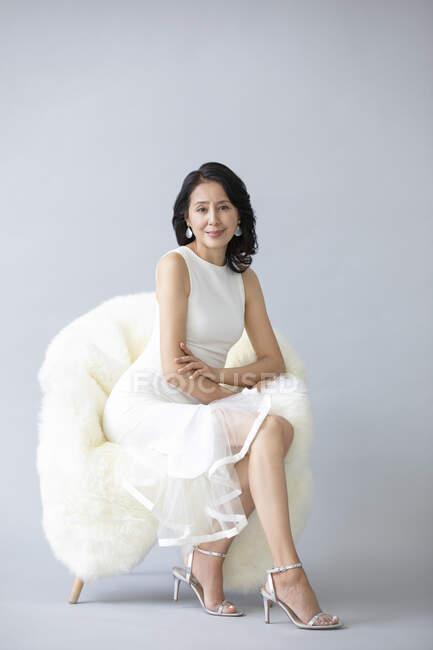 Belle femme chinoise posant sur fauteuil moelleux portant une robe blanche et des talons hauts — Photo de stock