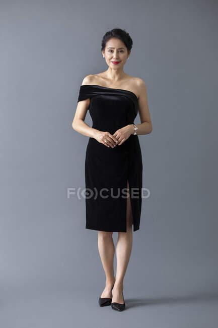 Beautiful mature chinese woman posing in black dress on gray studio background — Stock Photo