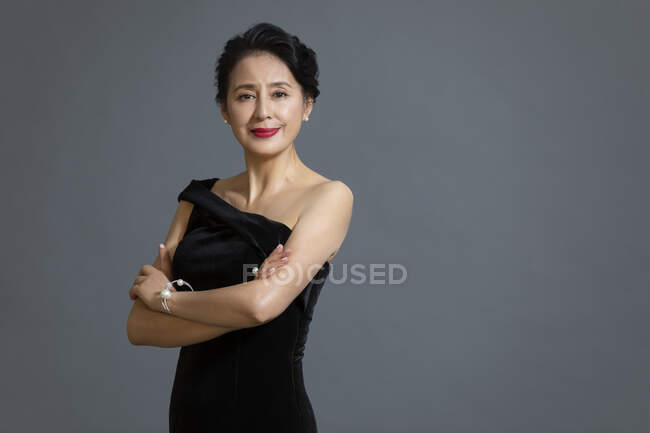 Beautiful mature chinese woman posing in black dress on gray studio background — Stock Photo