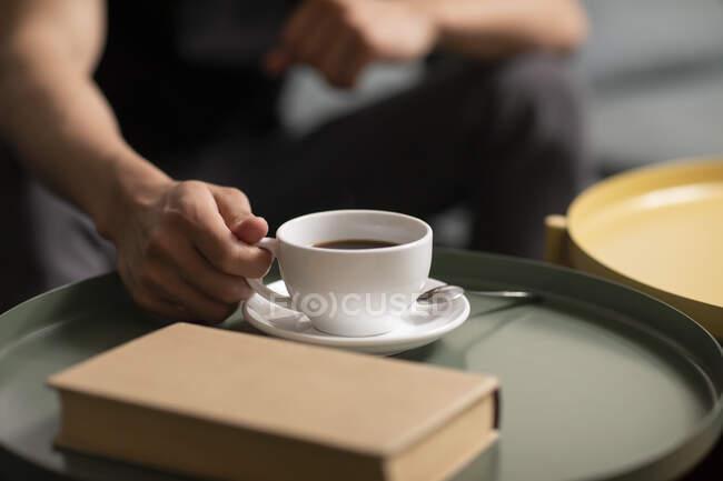 Мужская рука держа чашку кофе на столе с книгой — стоковое фото