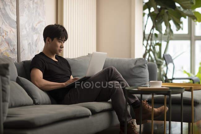 Junger chinesischer Mann sitzt mit Laptop auf Couch — Stockfoto