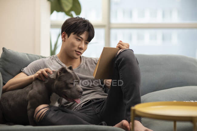 Young chinese man with dog sitting on couch and reading book — Stock Photo