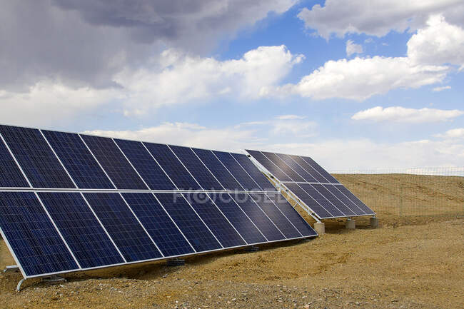 Solar panels on sandy land with blue cloudy sky — Stock Photo