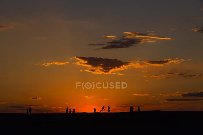 Beautiful cloudy sunset sky with people silhouettes — Stock Photo