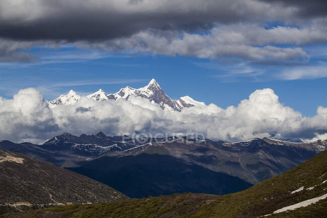 Snowy mountains and cloudy sky in Tibet, China — Stock Photo