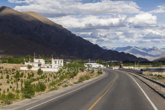 Escena con carretera, edificios, rocas y cielo nublado en el Tíbet, China - foto de stock